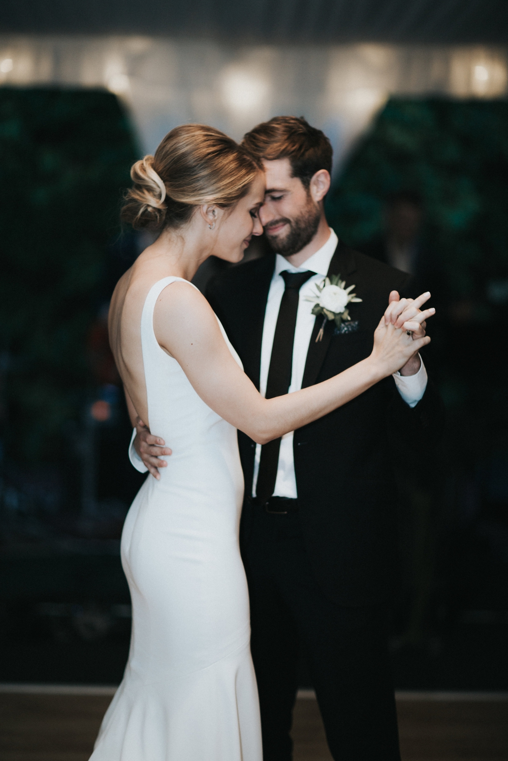 bride-leans-her-head-against-groom-during-first-dance