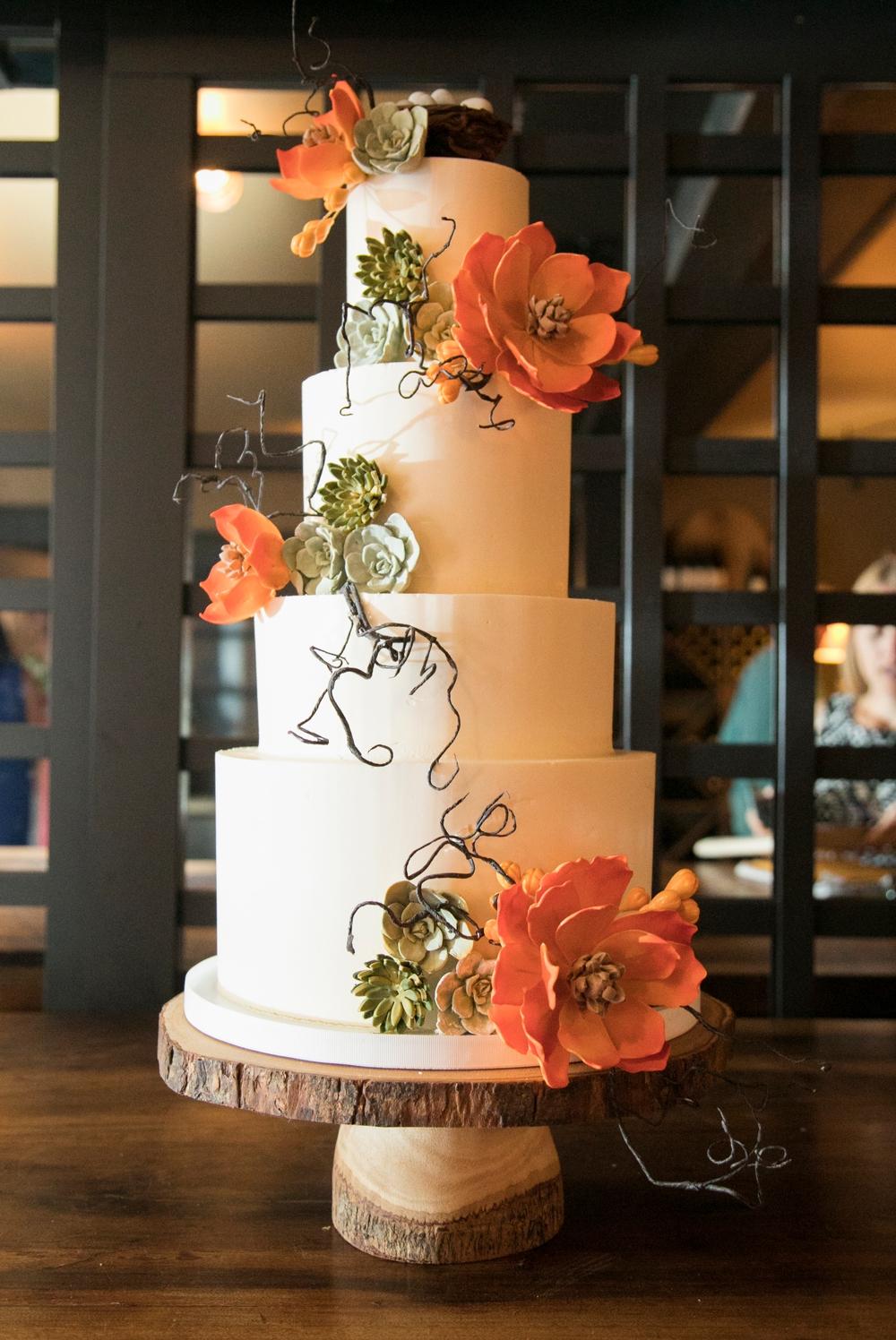 white-three-tiered-wedding-cake-with-large-orange-flowers