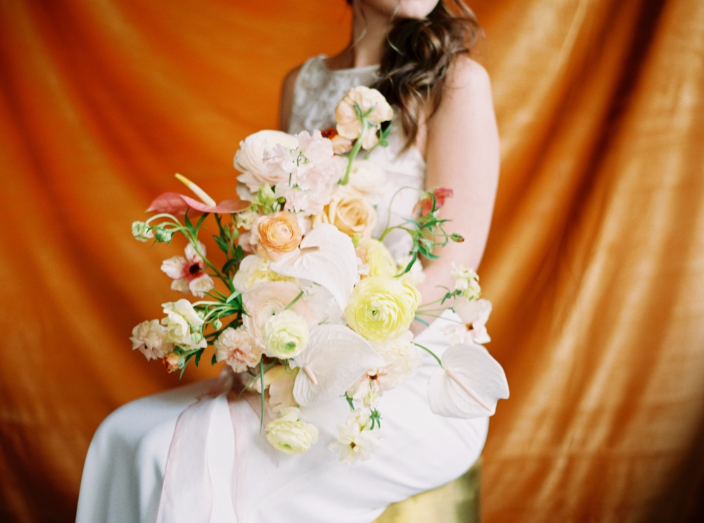 bride-seated-in-front-of-orange-backdrop