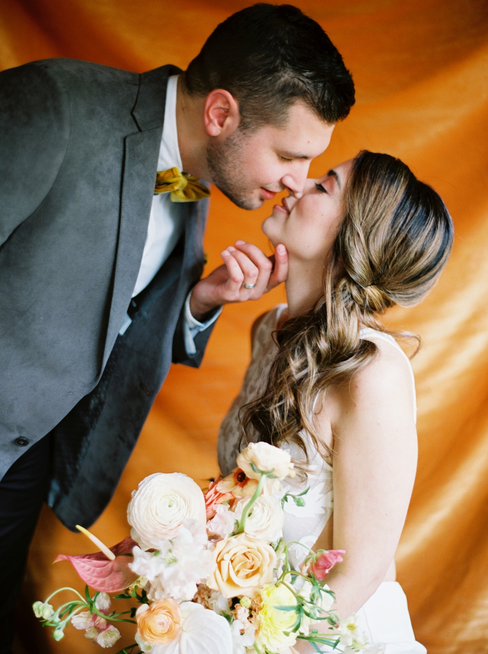 bride-and-groom-kissing-in-front-of-orange-backdrop
