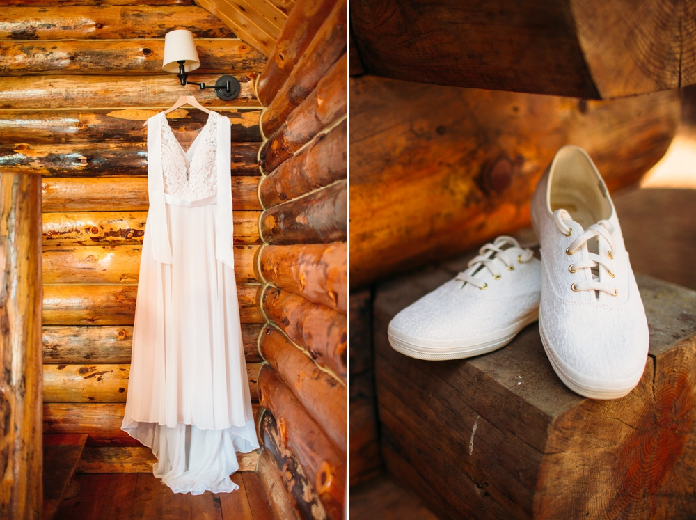 lace-wedding-dress-hanging-against-log-cabin-wall