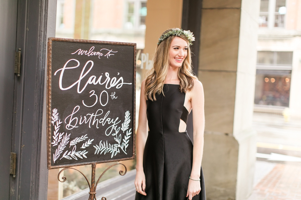 woman-in-black-dress-standing-by-birthday-sign